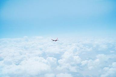 Airplane_Flying_Above_Clouds.jpg