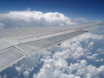 Airplane_wing_in_front_of_cumulus_clouds.jpg